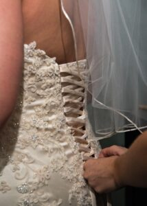 Back of brides dress getting laced up.