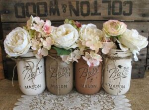 Four distressed mason jars painted in blush tones used as vases for DIY wedding decor.