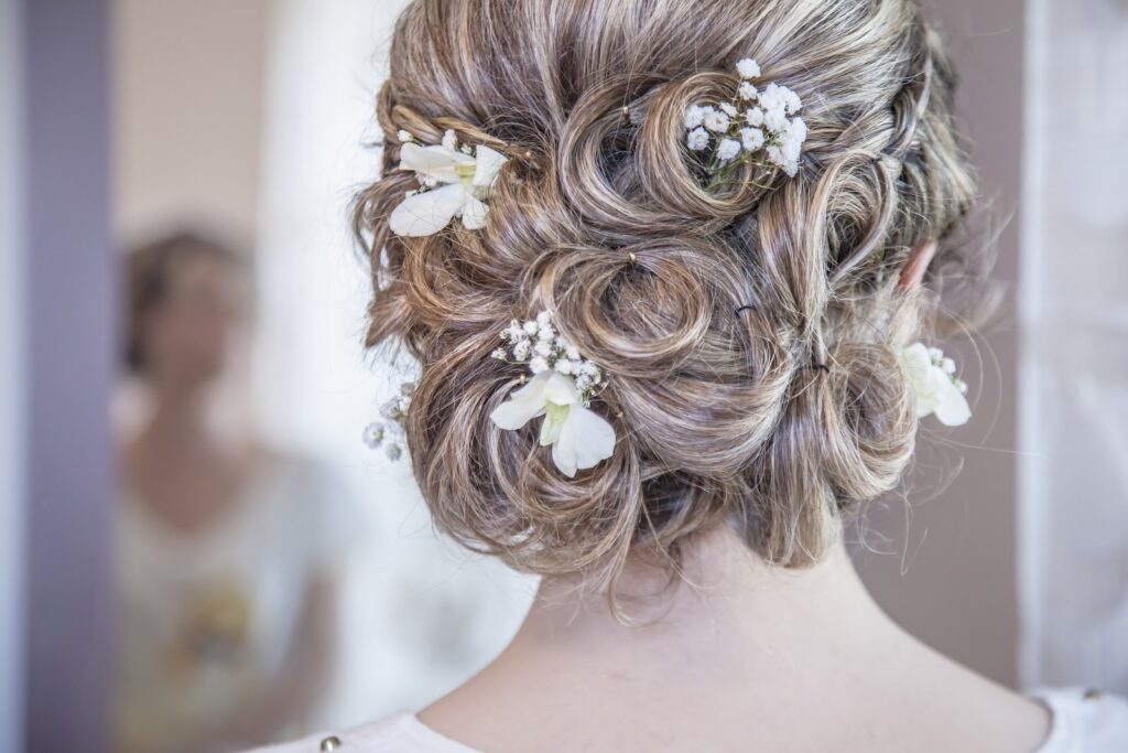 Brides hair in updo with white flowers.