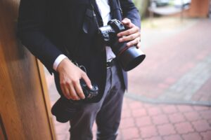 Man in dress clothes holding a camera in both hands.