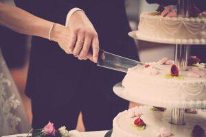 Couple cutting wedding cake.