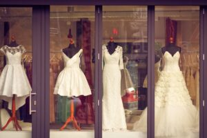 Four wedding dresses in window display.
