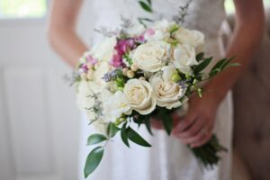 Bide holding her bouquet of white and pink flowers.