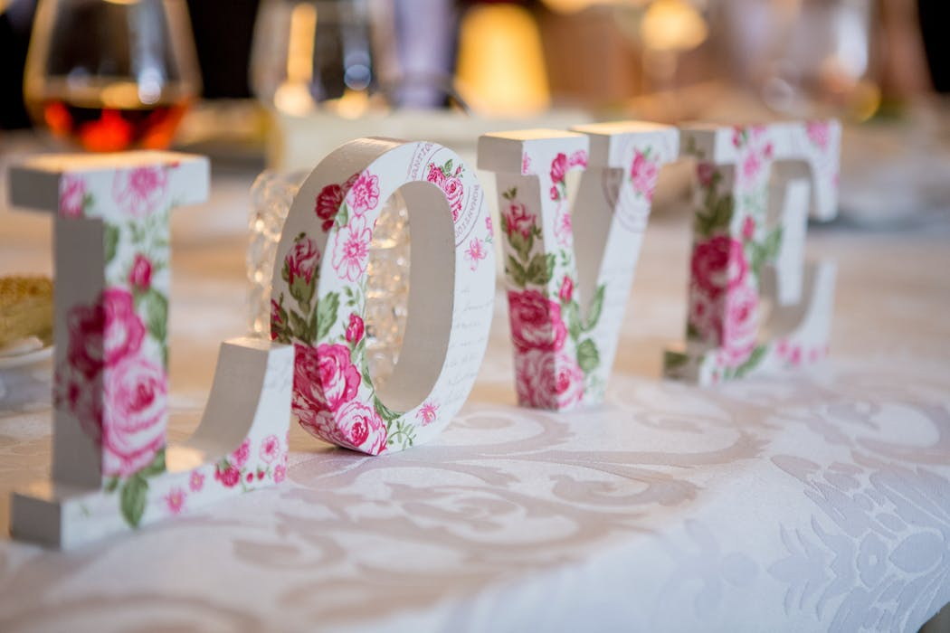 "Wooden letters that read ""love"" with roses painted on them."