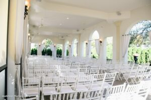 Outside wedding ceremony space with white chairs set up.