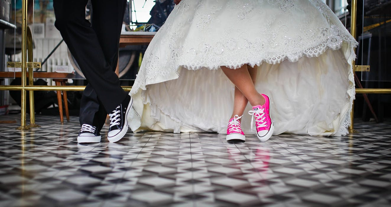 Bride and groom with converse on. Bride in pink and groom in black.