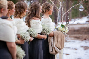 Bridesmaids holding flowers while standing in row in the snow.